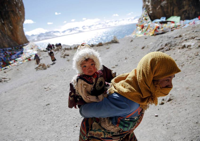 A well-dressed Tibetan woman carries his son to do Kora around Namtso Lake .