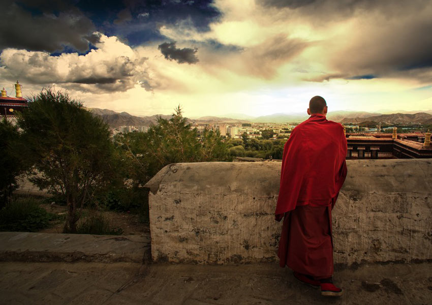 A monk gazes at Tashilumpo Monastery at twilight.