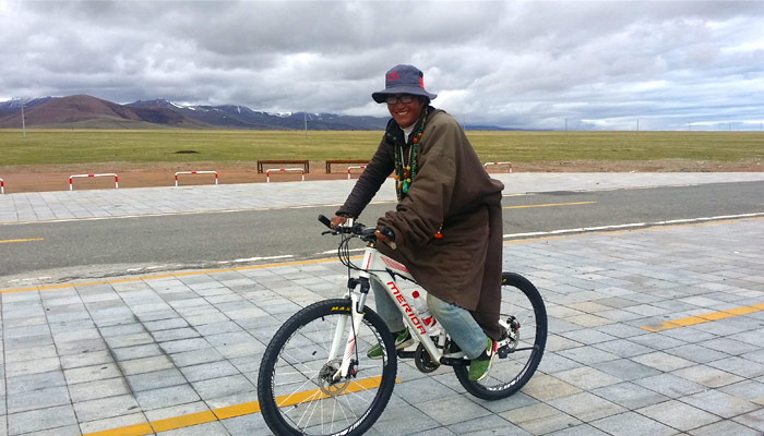 The local tibetan guide is cycling to Namtso Lake
