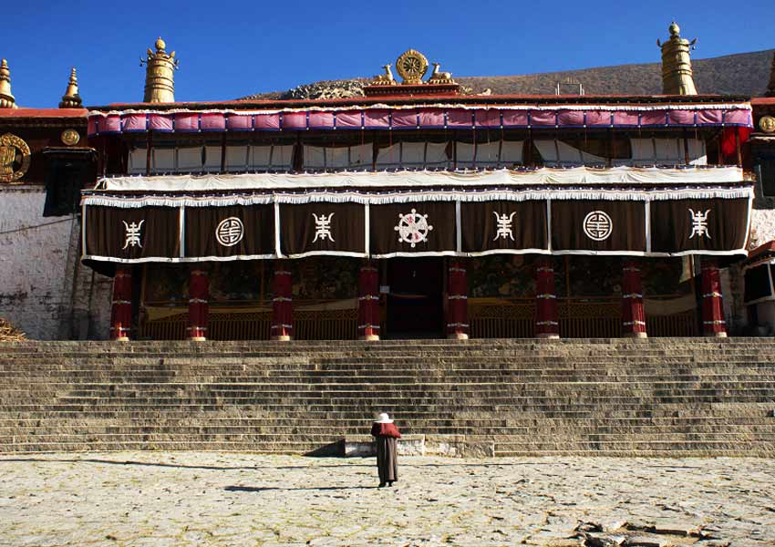 A local Tibetan bows down to show his respect to Buddhas in Drepung Monastery.